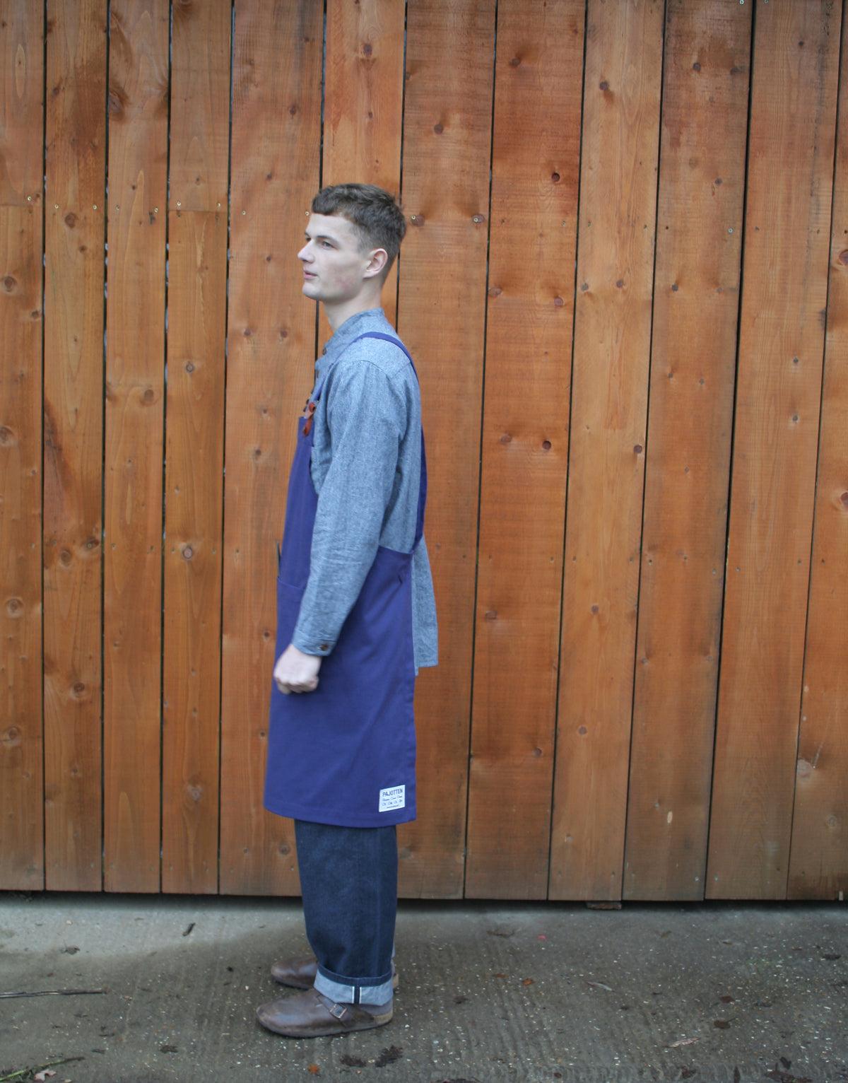 side v new of man wearing indigo apron against a wooden wall