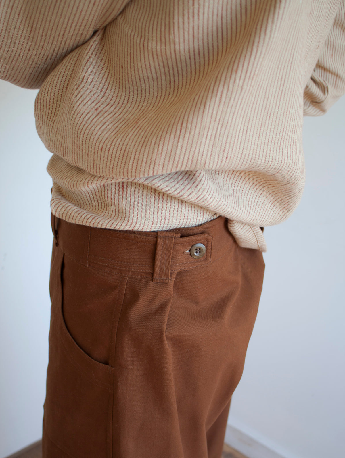 shop pajotten menswear close up image of the side view of a pair of chore trousers with side button fastening worn with a striped beige linen shirt