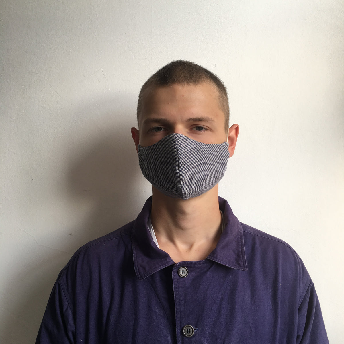 A man wearing a blue checked face mask made in the UK