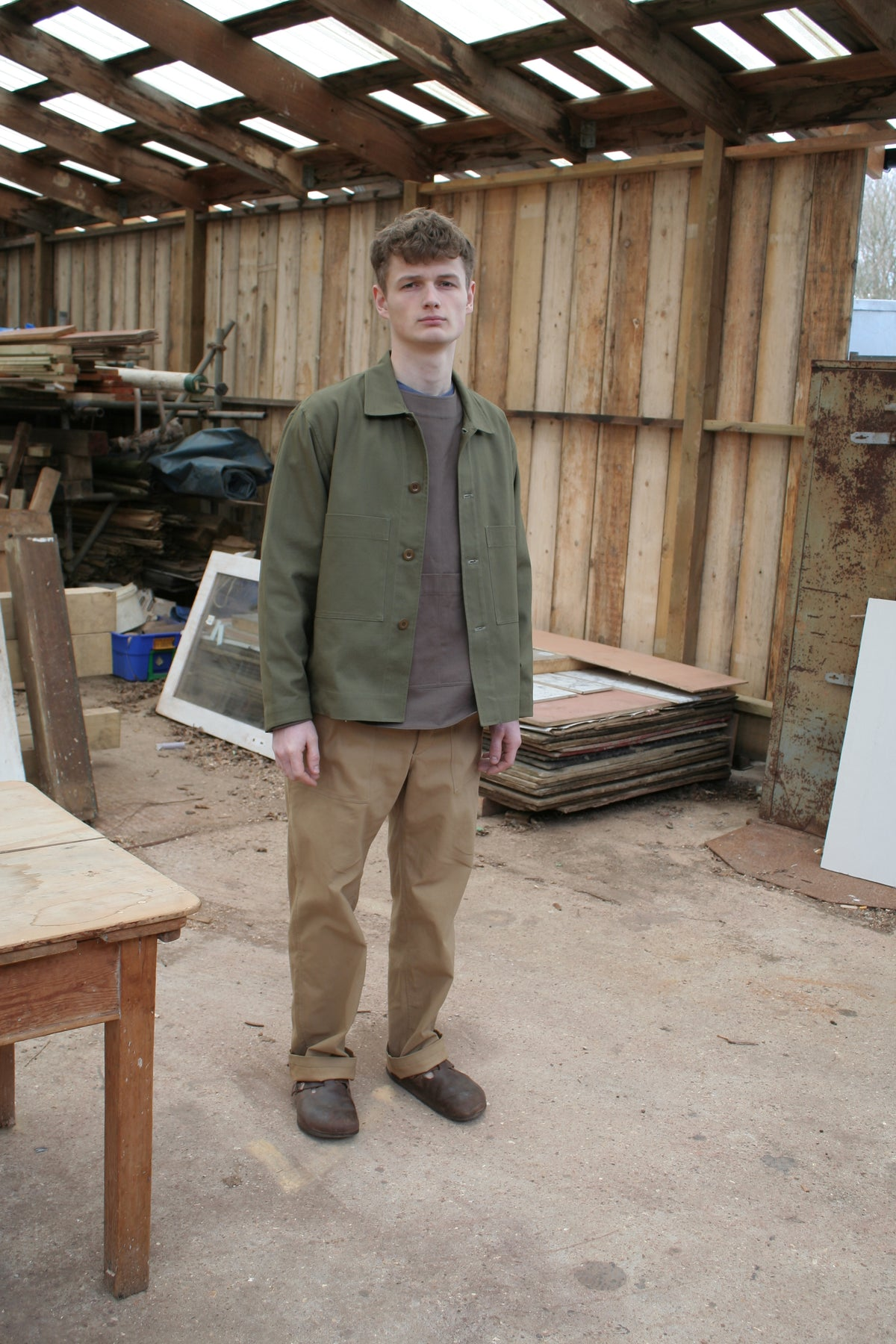 sustainable British menswear sage cotton workwear jacket with brown artists top and tan cotton chore trousers