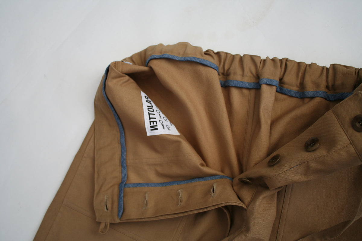 CLOSE UP OF THE INSIDE OF THE MENS TAN COTTON CANVAS SHORTS