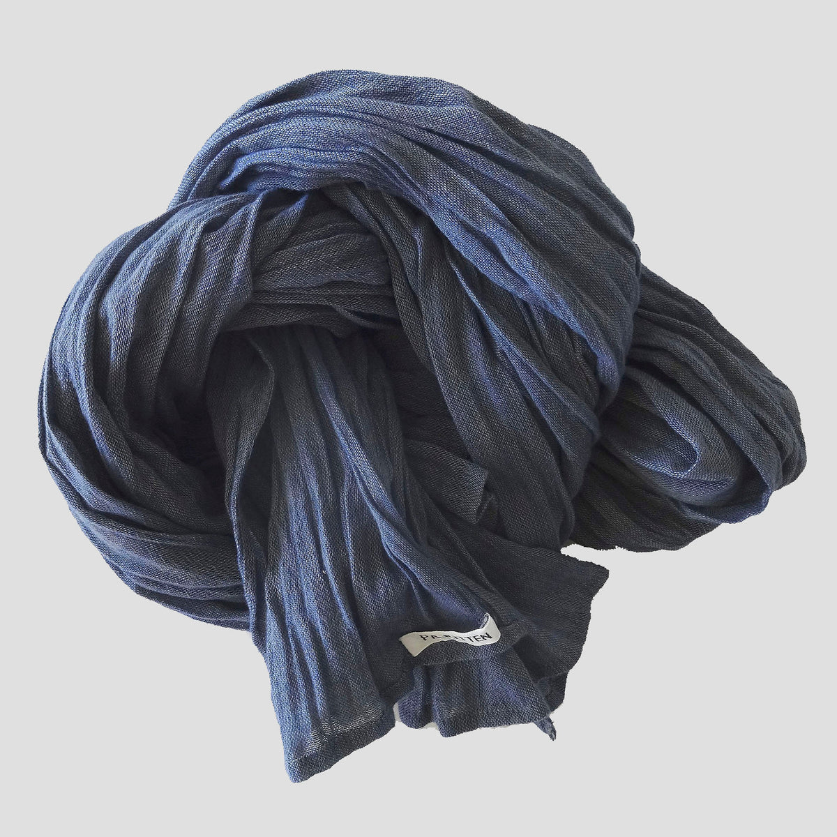 a blue organic cotton scarf rolled up on a table