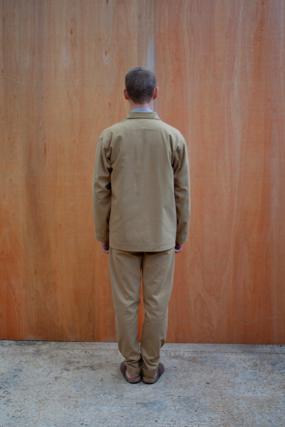 a young man standing against a wooden wall wearing a traditional chore jacket made in a sustainable tan  brushed cotton canvas