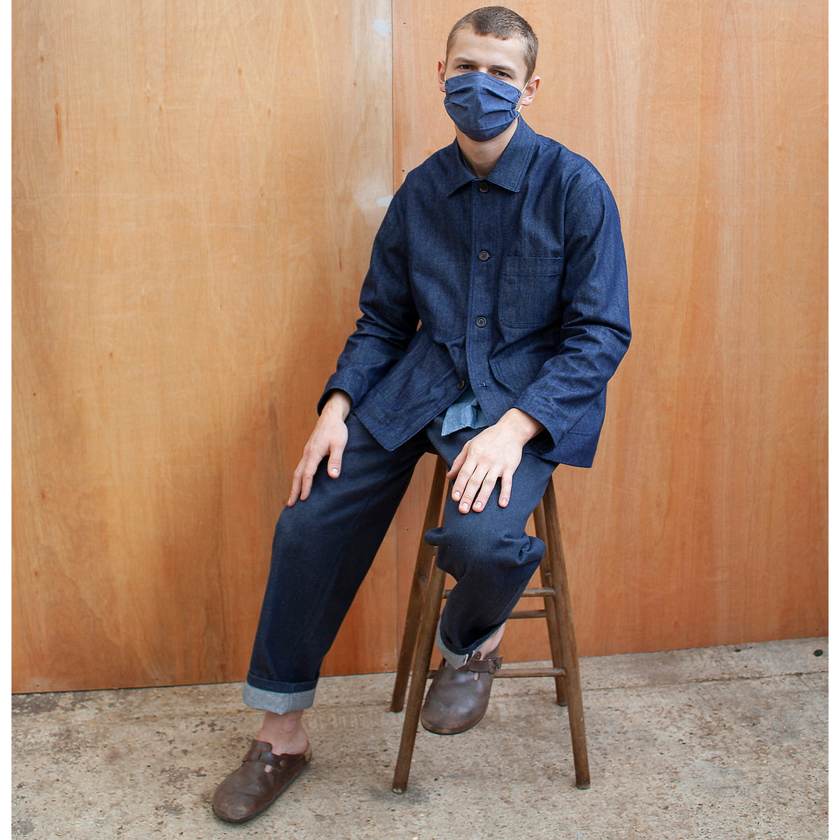 man wearing a face mask and a traditional chore jacket made in denim, he is sitting on a wooden stool against a wooden wall