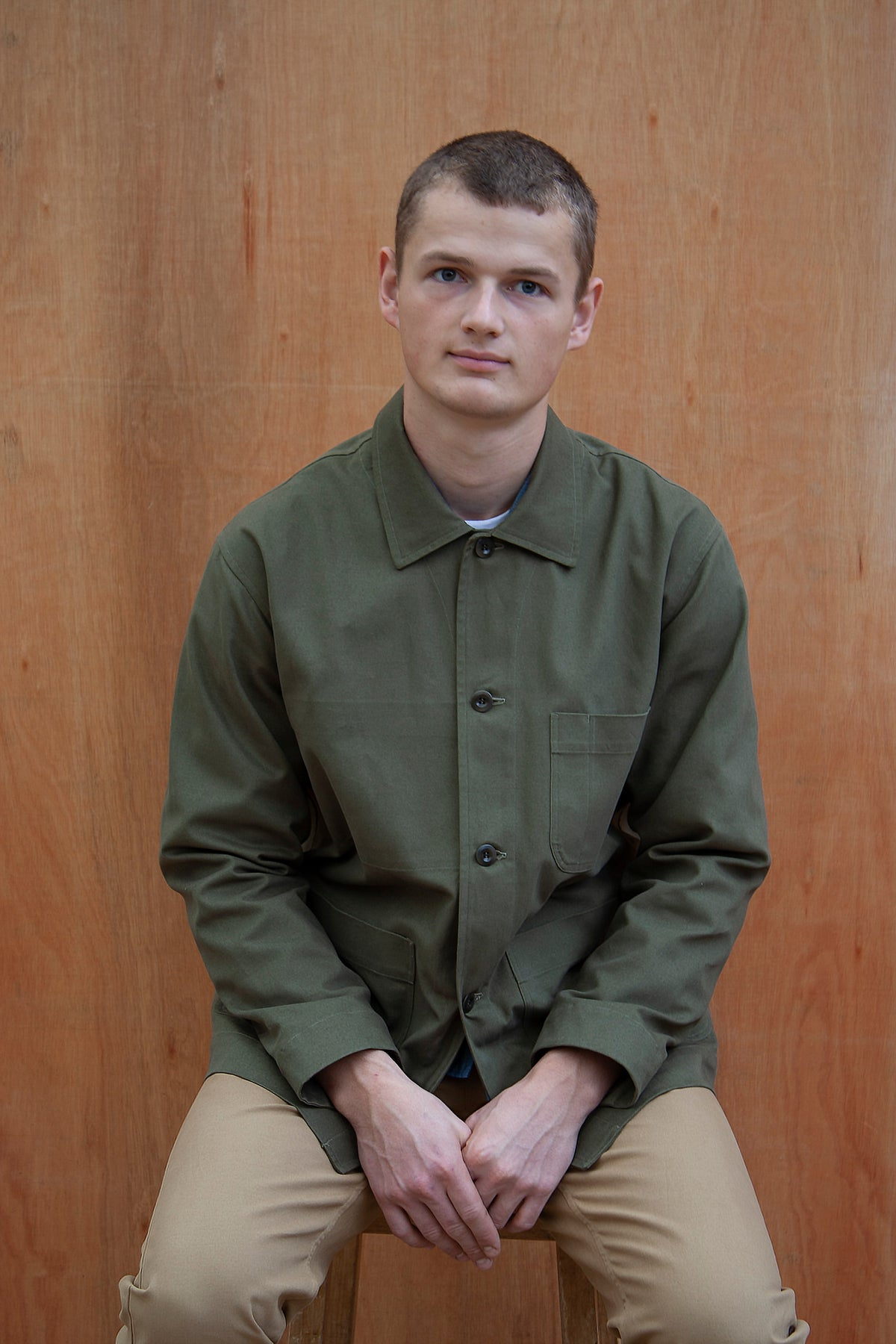 a young man sitting against a wooden wall wearing a traditional chore jacket made in a sage green  brushed cotton canvas