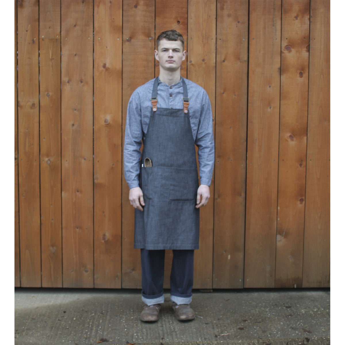 young man wearing a denim apron with leather fastenings