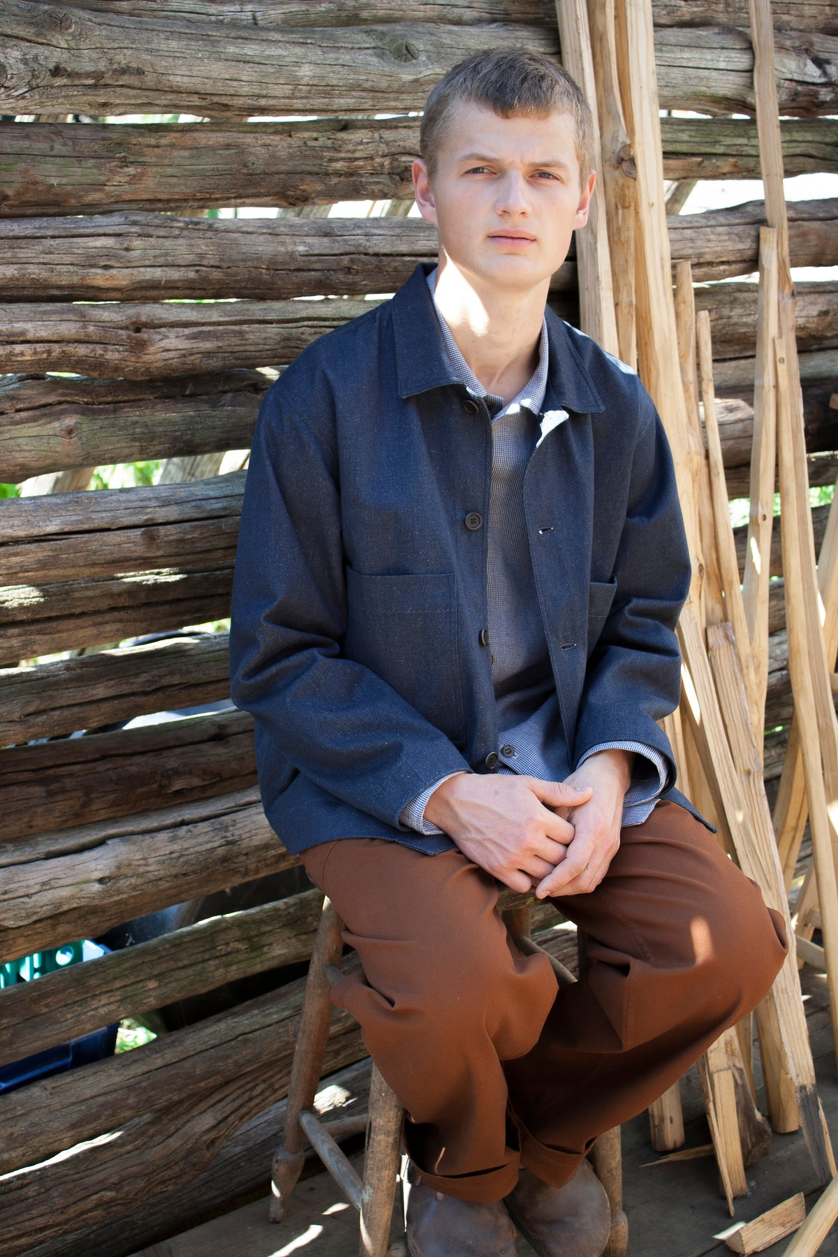 Young man sitting on a stool outside on a sunny day, he is sitting against a wooden wall, and next to some striped wooden poles, he is looking straight at the camera and is wearing a pair of brown trousers and a simple denim workwear jacket
