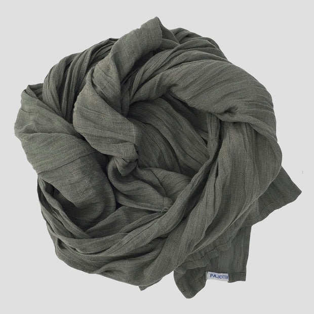a green organic cotton scarf rolled up on a table