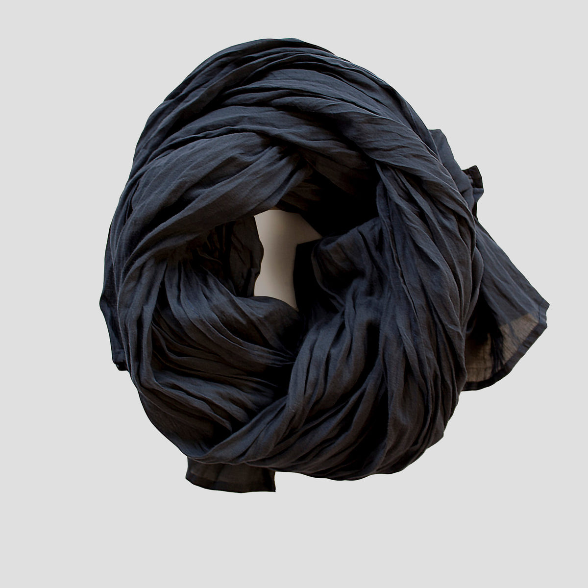 a lightweight navy  cotton scarf rolled up on a table