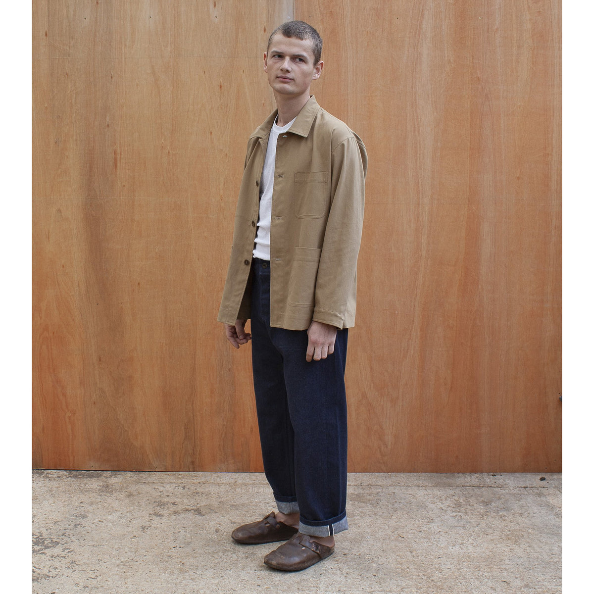 a young man standing against a wooden wall wearing a traditional chore jacket made in a sustainable tan brushed cotton canvas  Edit alt text