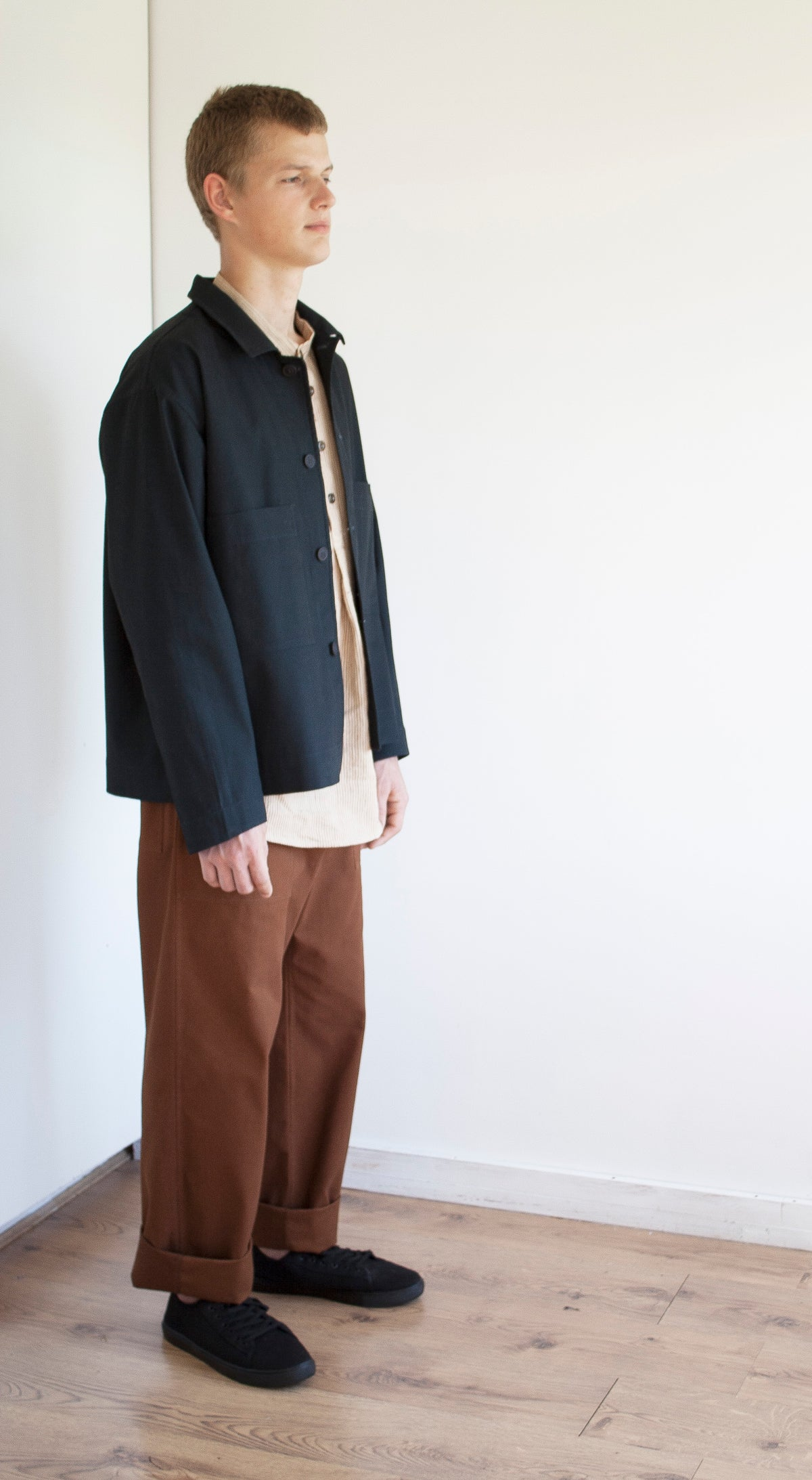 the side view of a young man with short hair, he is standing in the corner of a white room and he is wearing a pair of baggy rust workwear trousers, a grandad shirt and a simple jacket in a soft navy brushed cotton canvas.
