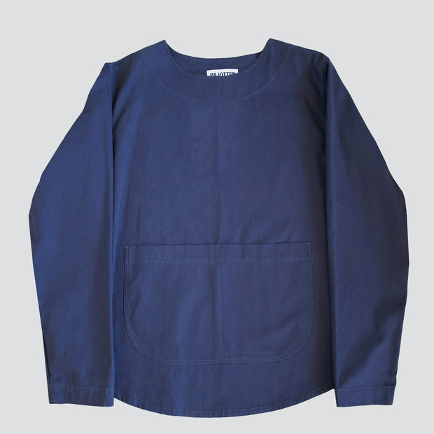 front view of an artist top in a blue cotton drill, with deep bucket pocket