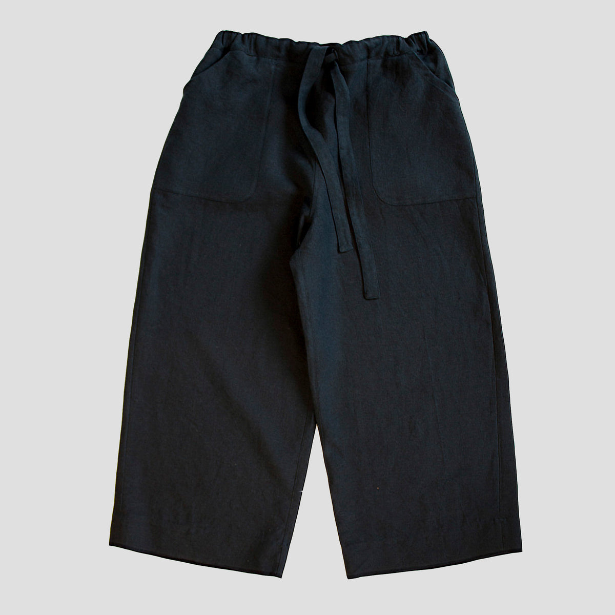 front view of a pair of dark navy heavy linen womenswear trousers with an elasticated waist and deep pockets
