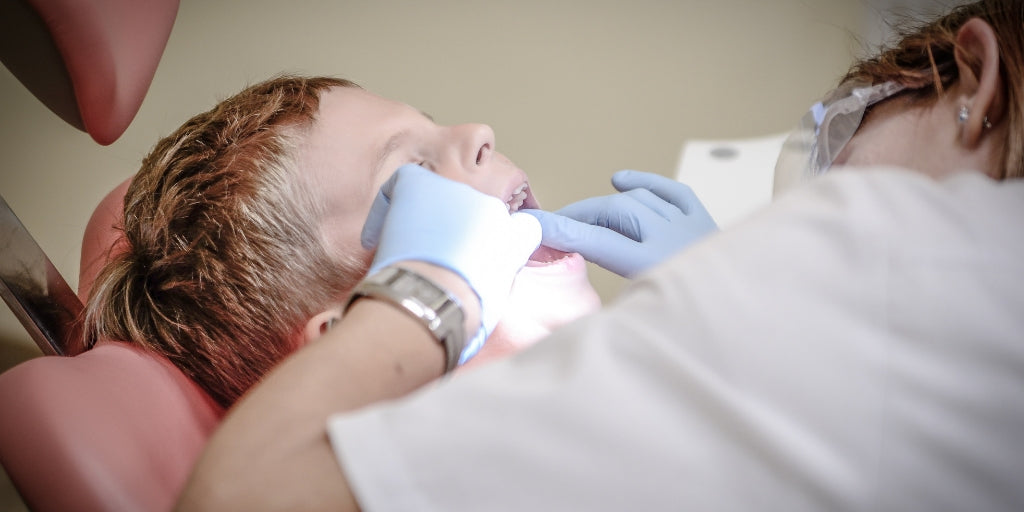 Dentist looking in kid's mouth