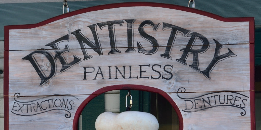 "Old style sign for dentist: ""Denistry, painless, extractions, dentures"""