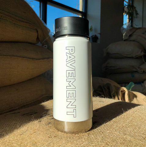 sexy Klean Kanteen insulated coffee mug with Pavement Coffeehouse logo glistening in the morning sun at our roastery in Boston