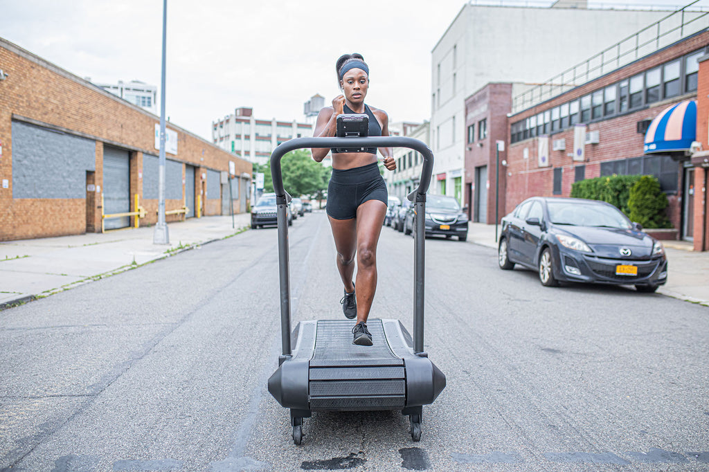View from the front of a person running on the Assaultrunner treadmill positioned in the middle of the street.