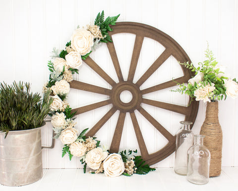 Wood wheel cutout with white sola flowers