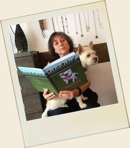 Woman reading Galunker - The illustrated book starring a pitbull, with a dog in her lap