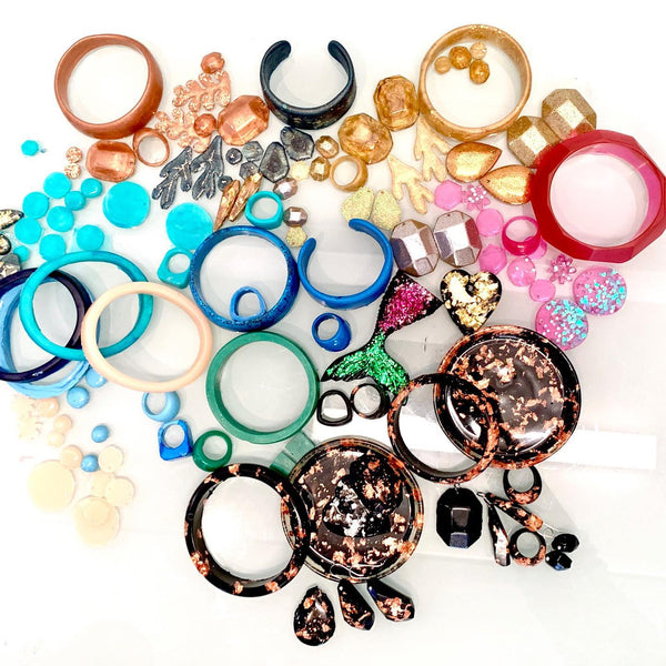 a large pile of colourful resin bangles, rings and earrings made in a workshop.