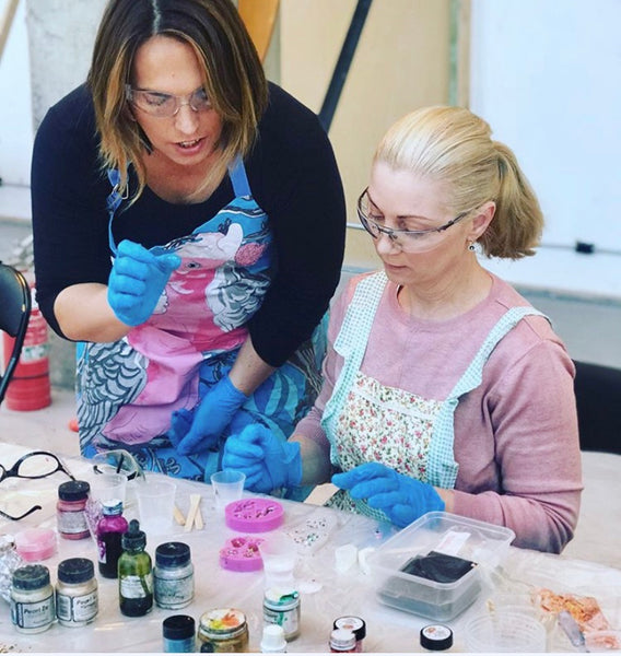 Two women wearing gloves, one sitting the other standing and bent over talking to the woman sitting. Both are looking at pink silicone moulds on table. on the table are bottles of dys and pots of pigments