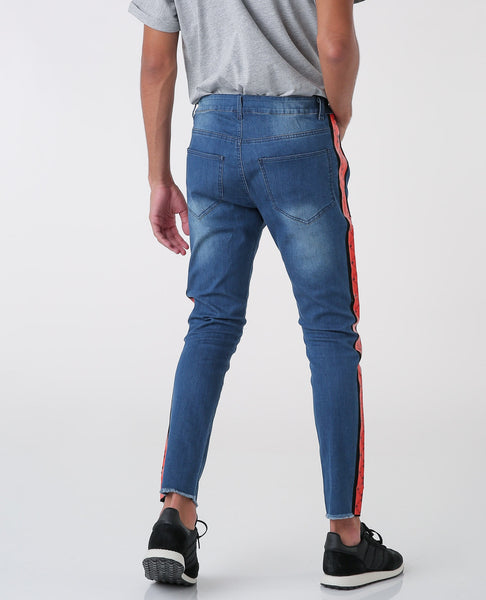 blue jeans with House of Cenmar orange pattern on the sides.