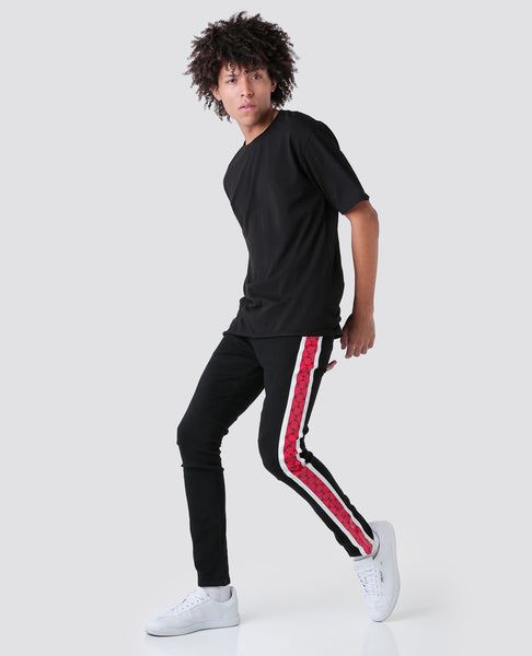 black jeans with House of Cenmar red pattern on the sides.