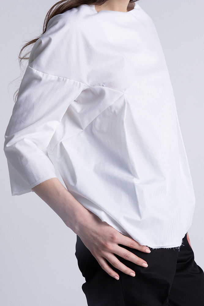 Side of Casa Como white poplin blouse with half sleeves and curved hem.