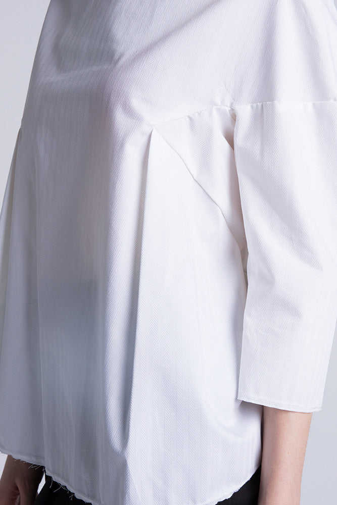 Close-up of Casa Como white poplin blouse with half sleeves and curved hem.