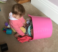 baby girl playing, playing with laundry basket