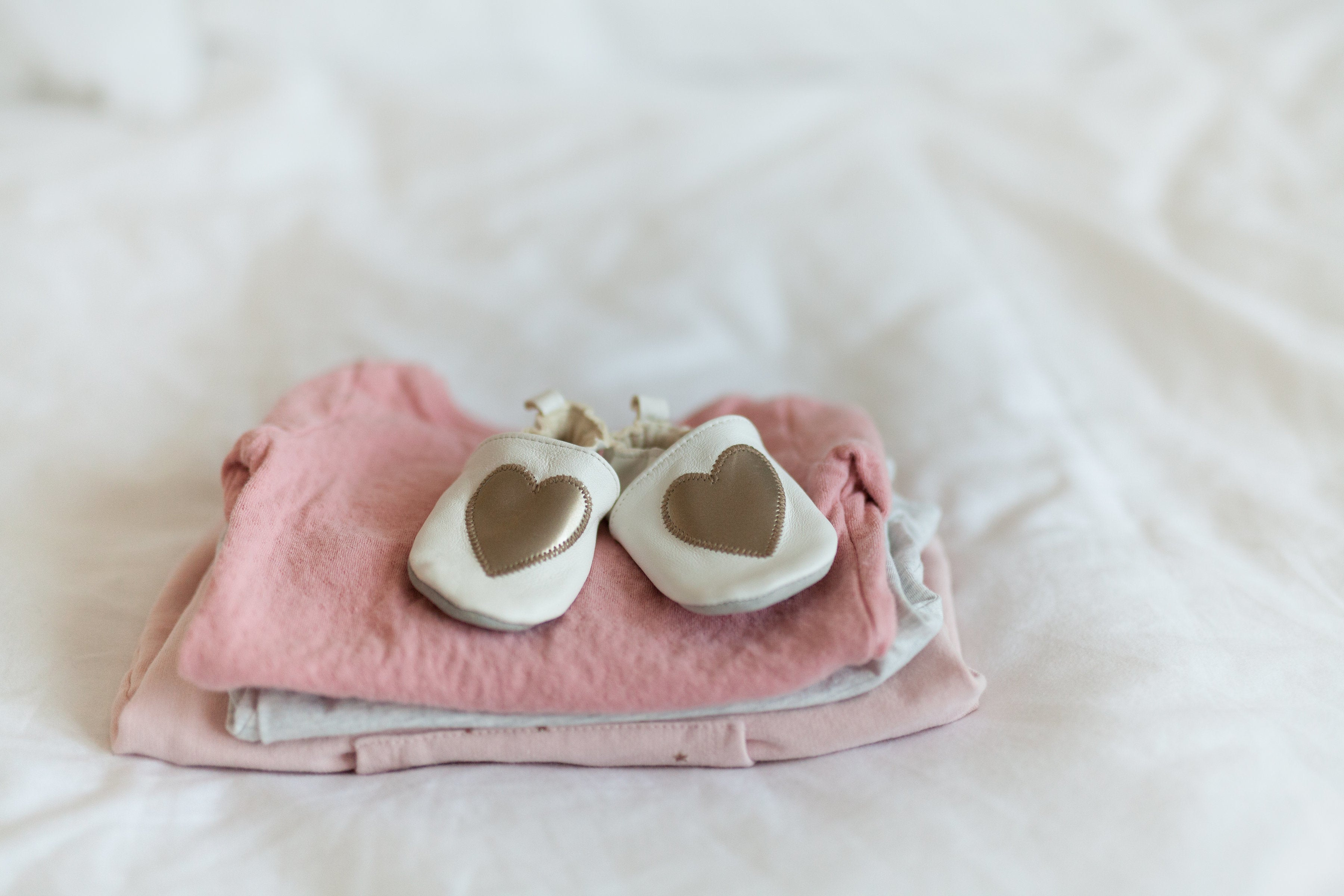 folded baby clothes on top of a bed
