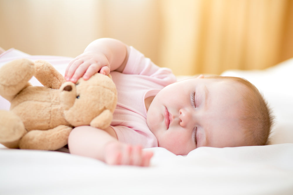baby sleeping with a soft plush teddy