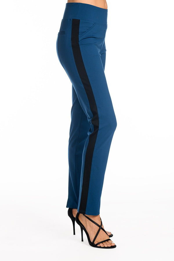 One model wearing a ladies technical stretch tuxedo pant for long legs in azure with a black side stripe on a white background.