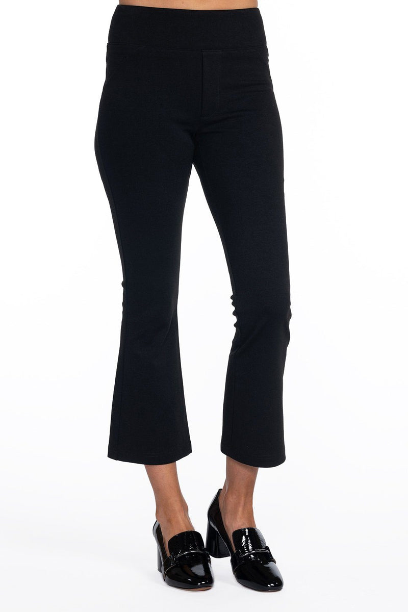 One model wearing a ladies flared and cropped technical stretch pant in black on a white background.