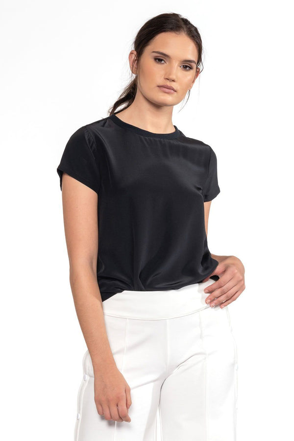 One model wearing a ladies silk, short-sleeve tee in black on a white background.