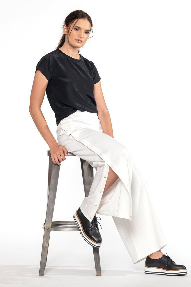 One model wearing a ladies silk, short-sleeve tee in black on a white background, by The Cause Collection.