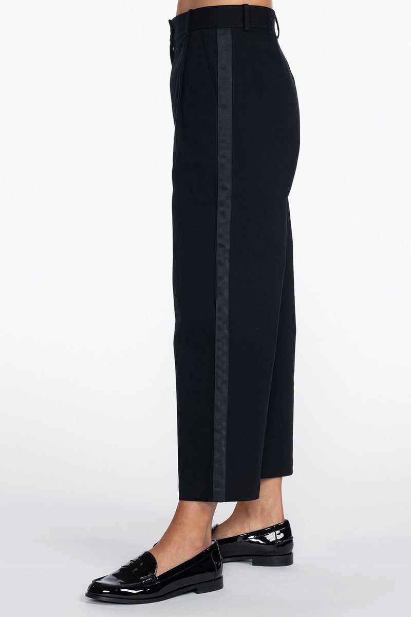 One model wearing a ladies flared and cropped cotton pant in black with side stripe and back pocket ribbon detailing.