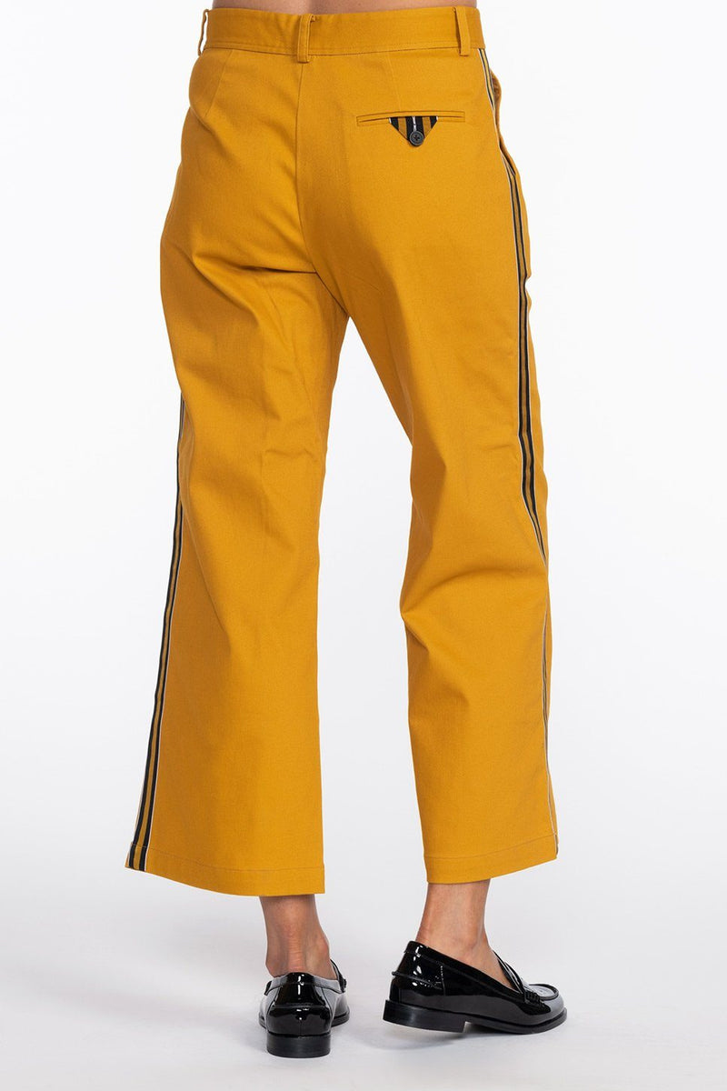 One model wearing a ladies flared and cropped cotton pant in curry with side stripe and back pocket ribbon detailing.