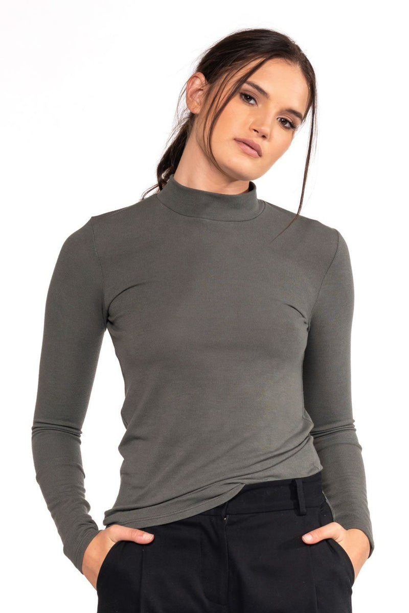 One model wearing a ladies mock neck knit top in army on a white background.