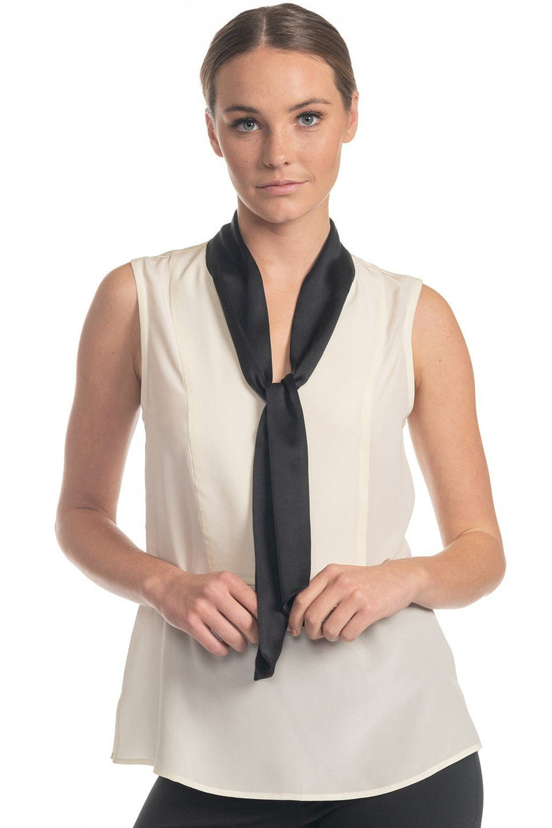 One model wearing a tie neck silk shell in cloud on a white background.