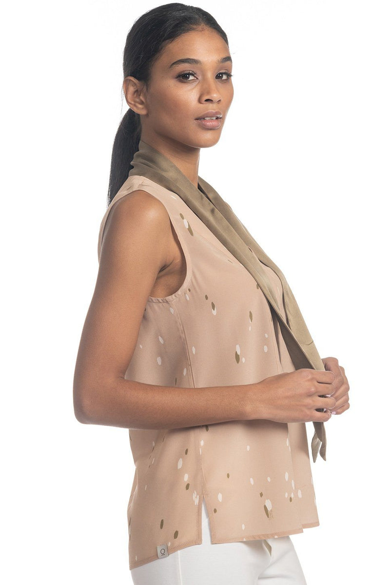 One model wearing a ladies tie neck silk shell in sand on a white background.