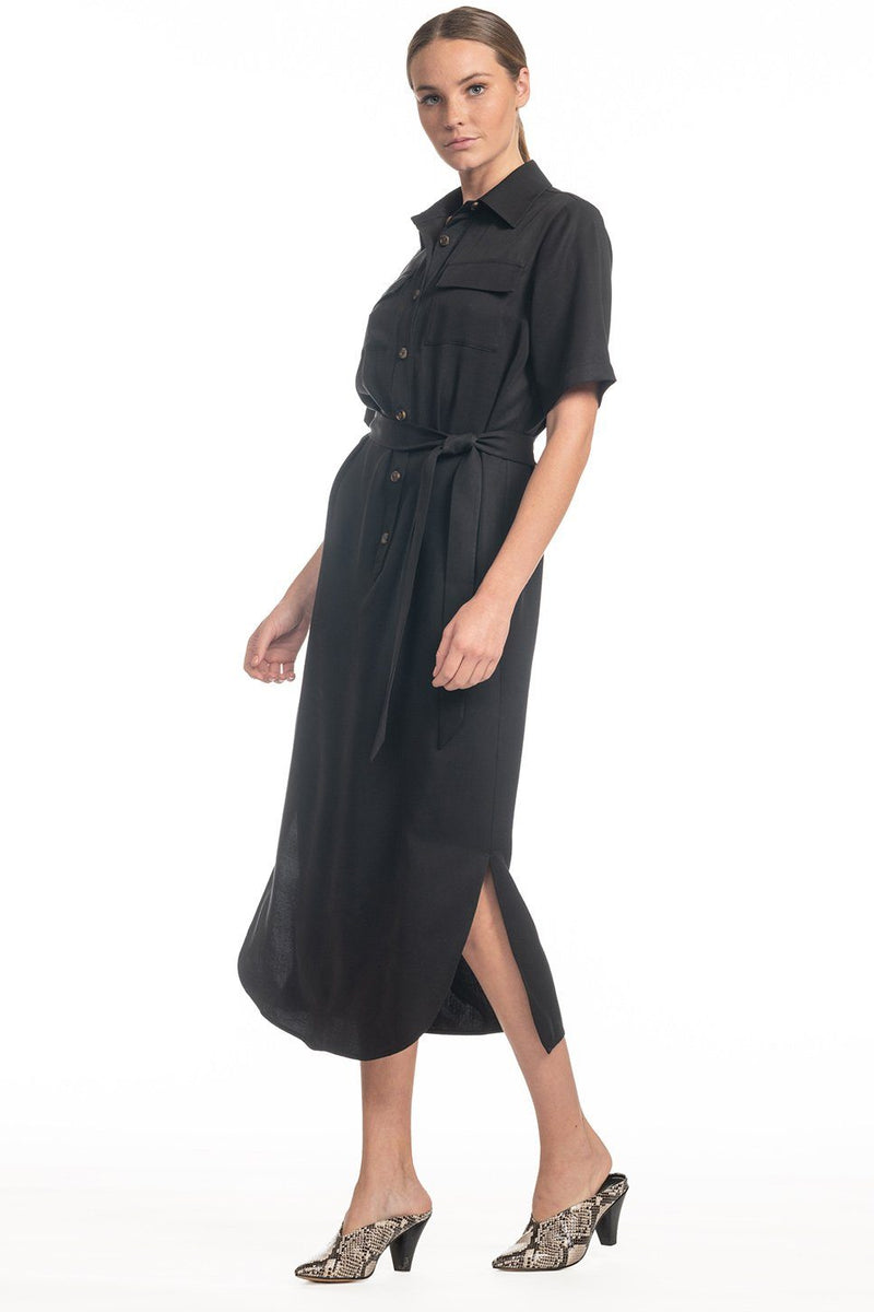 57d7e8be26 One model wearing a ladies utility tie waist shirt dress in black on a  white background