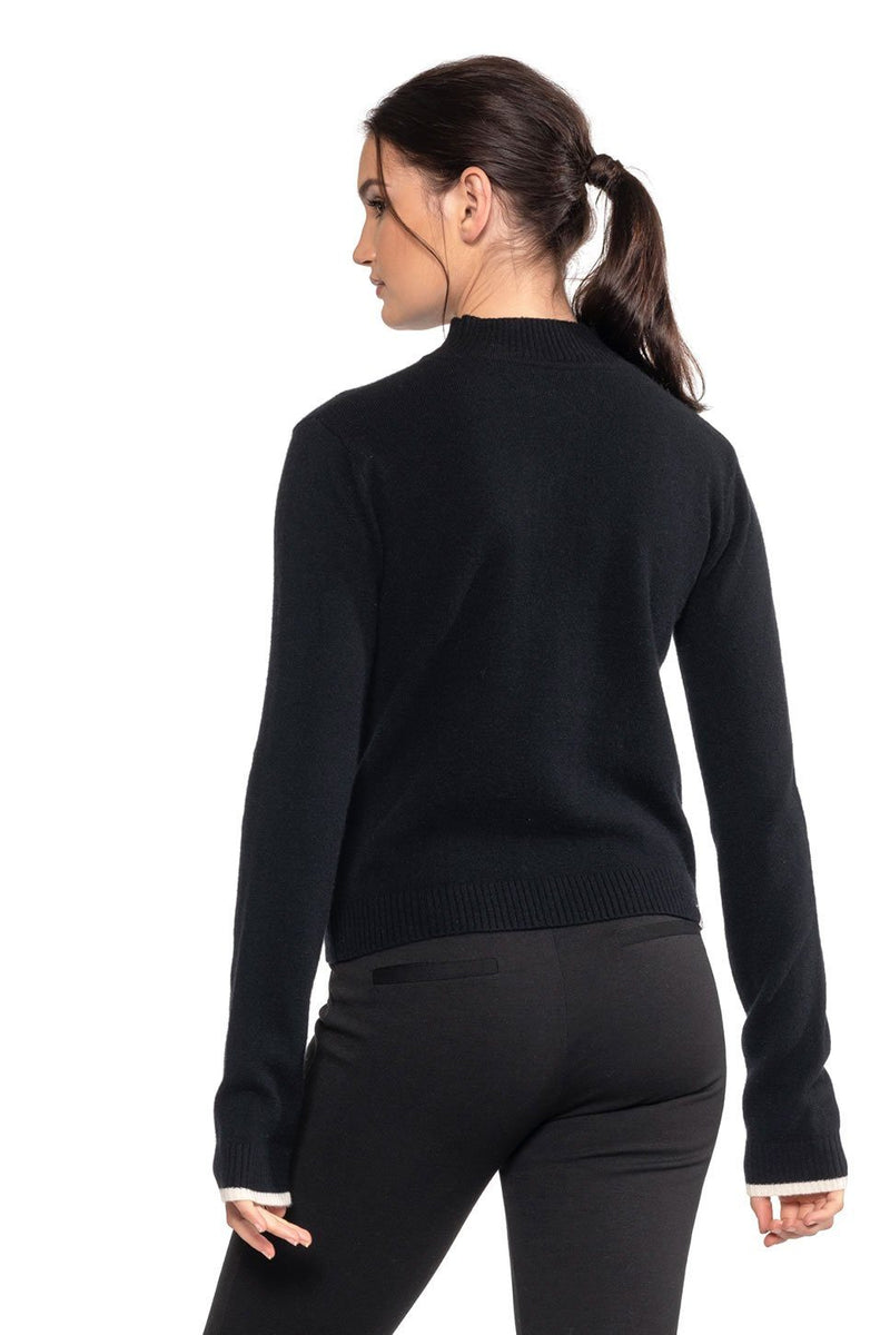 One model wearing a ladies mock neck 100% cashmere sweater in black on a white background.