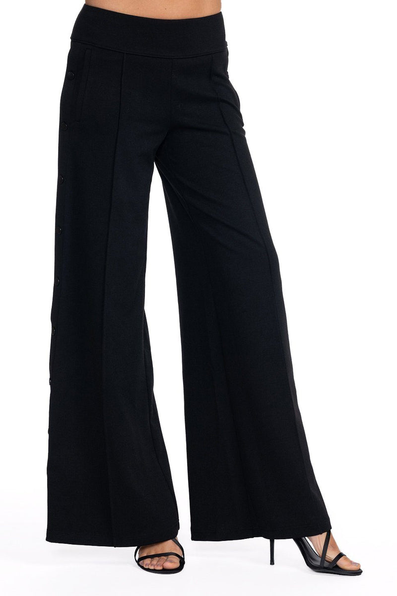 One model wearing a ladies technical stretch, wide-leg pant with side snaps in black on a white background.