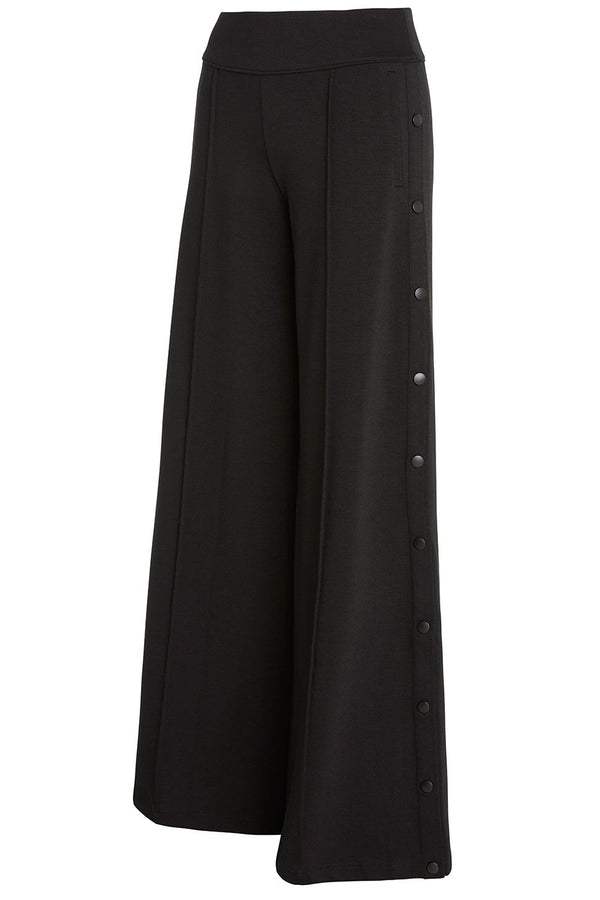 A ladies technical stretch, wide-leg pant with side snaps in black on a white background.
