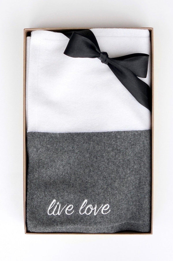 "One ladies embroidered ""live love"" 100% cashmere scarf in grey and white in a box with a black bow on a white background."