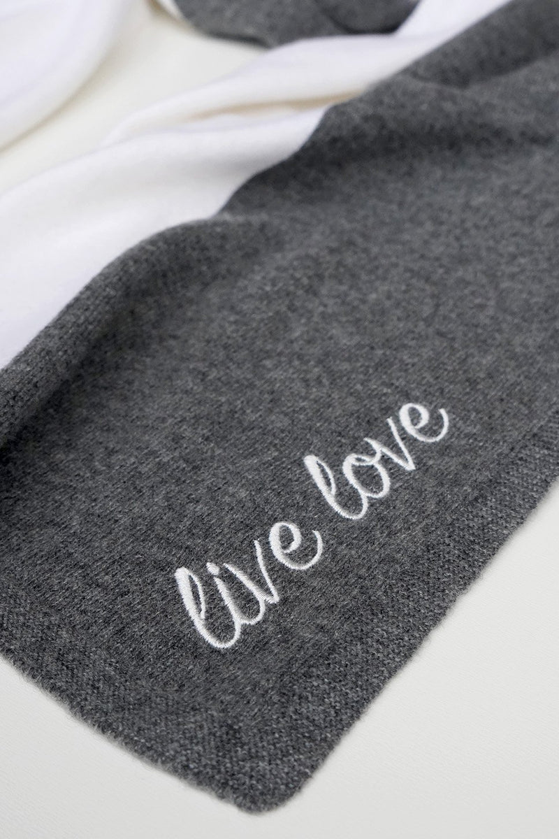 "One close up of the ""live love"" embroidery on the ladies 100% cashmere scarf in grey and white."