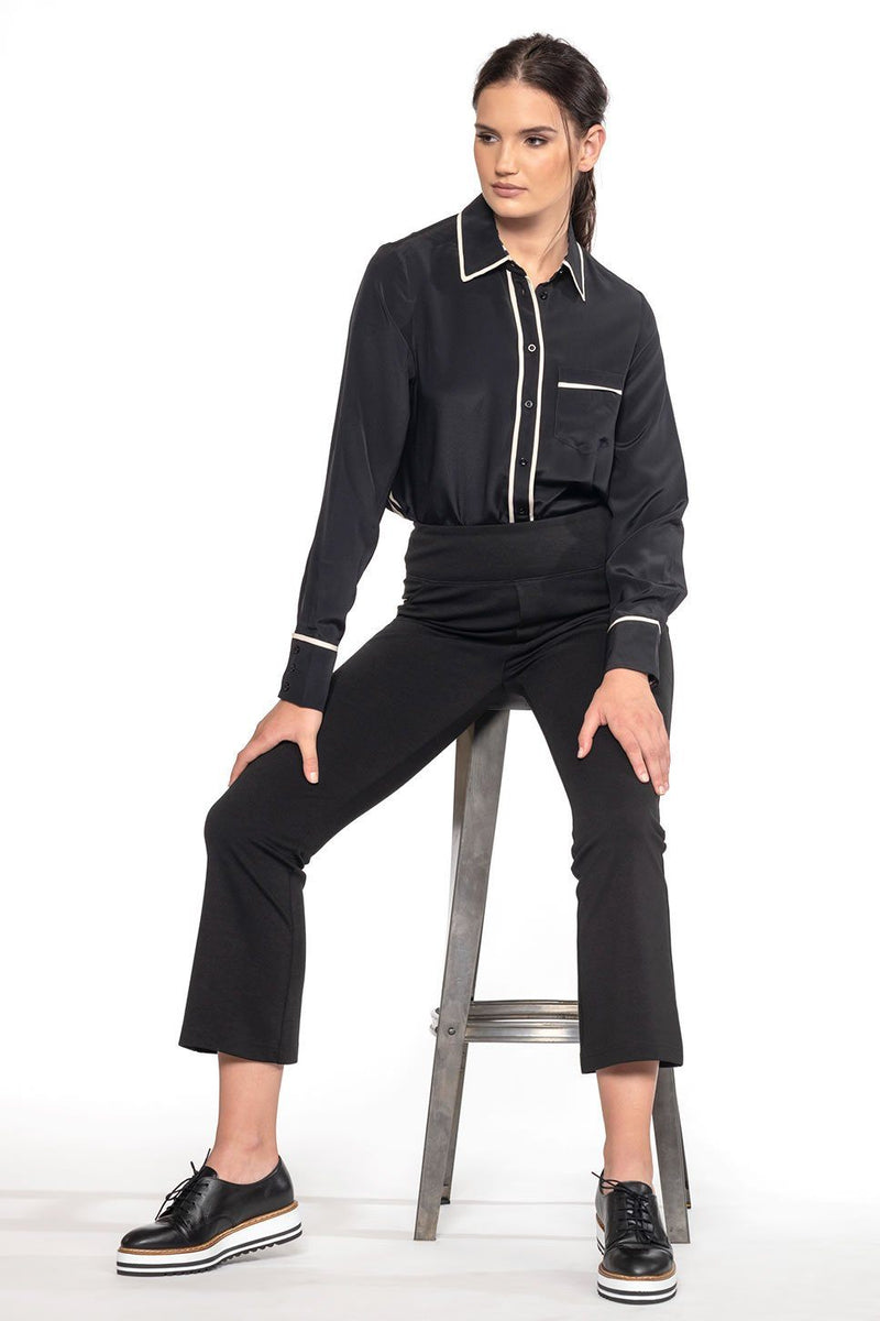 One model wearing a ladies button-down 100% silk blouse in black on a white background.