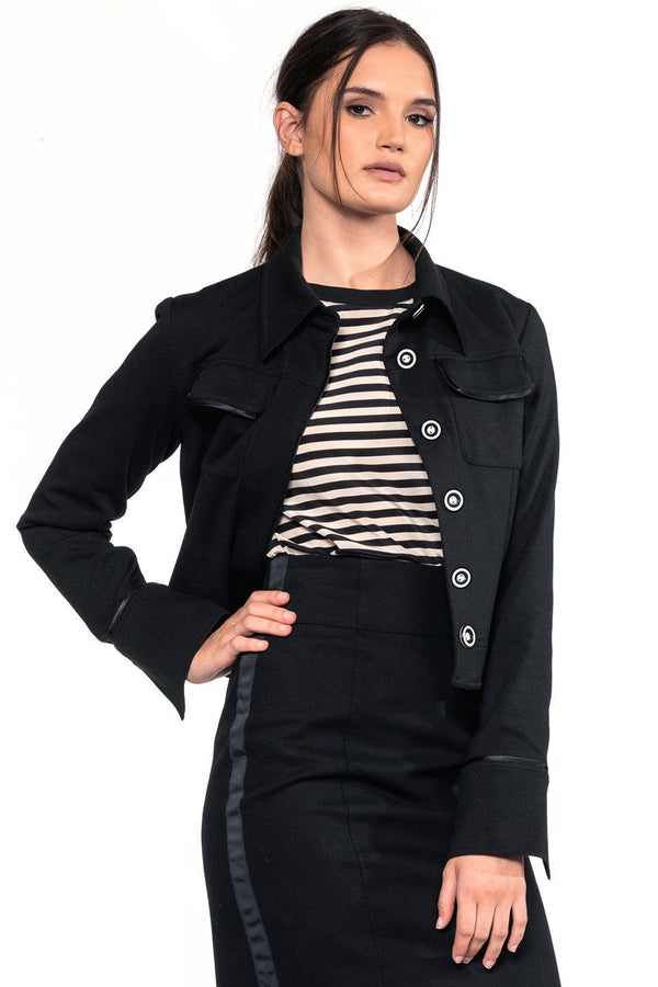One model wearing a ladies cropped, technical stretch blazer in black on a white background.
