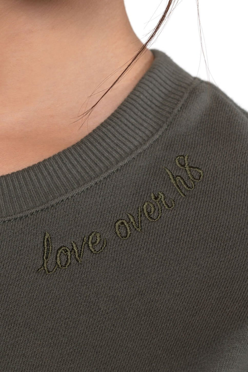 "One model on a white background wearing a ladies French terry sweatshirt in army embroidered with ""Love Over H8"" at the front neck."